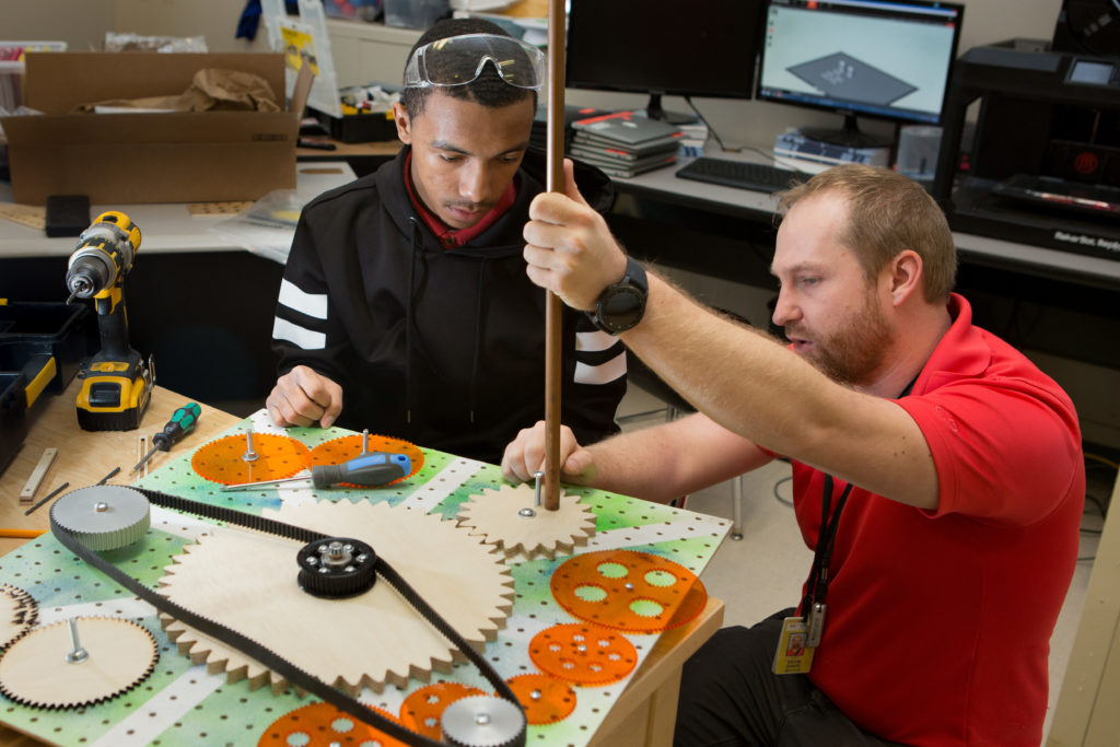 Male teacher helps male student with engineering project