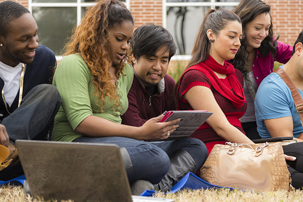 Multi-ethnic group of college student friends hang out on campus.  They are using digital tablets and laptop computers as they sit on grass in front of a school building.  The group of university friends are enjoying the fall afternoon visiting together.