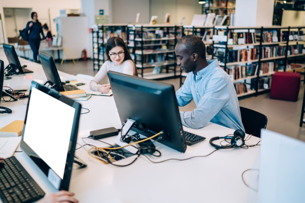 Attentive young multiethnic man and woman in casual outfit talking and doing homework while sitting together at table with computer with empty screen in library