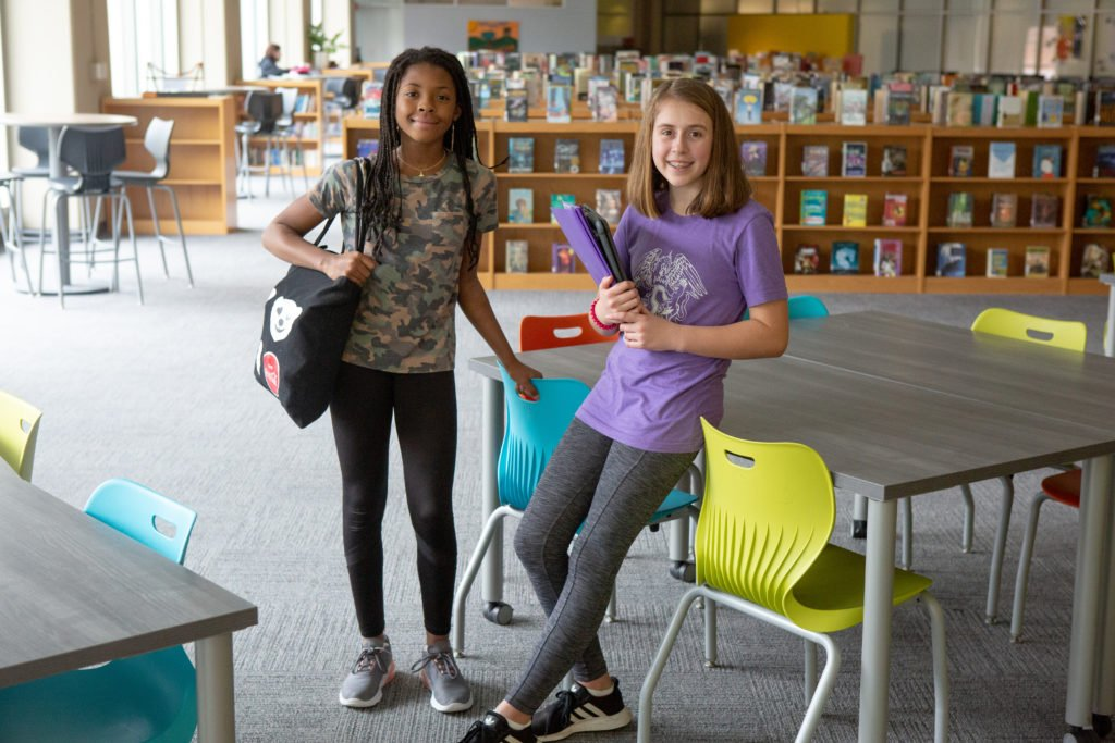 Two seventh-grade students pose for a photo with their notebooks in the library.